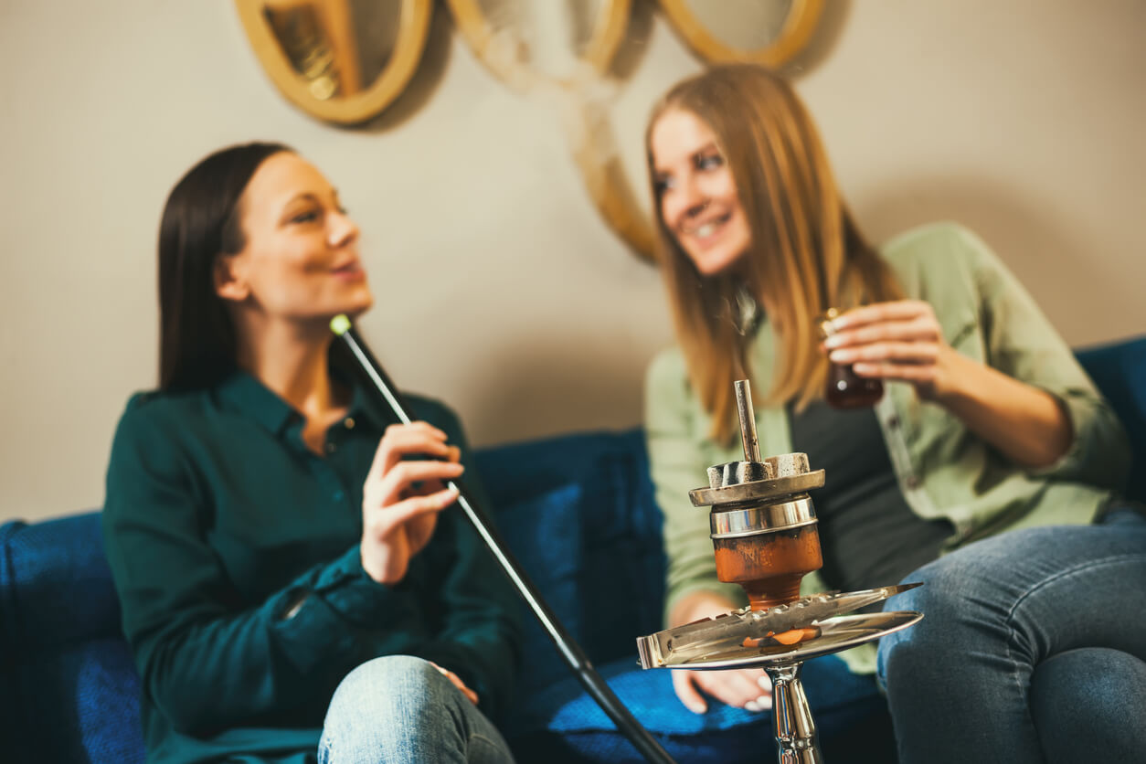 Two women in caffe inhaling hookah
