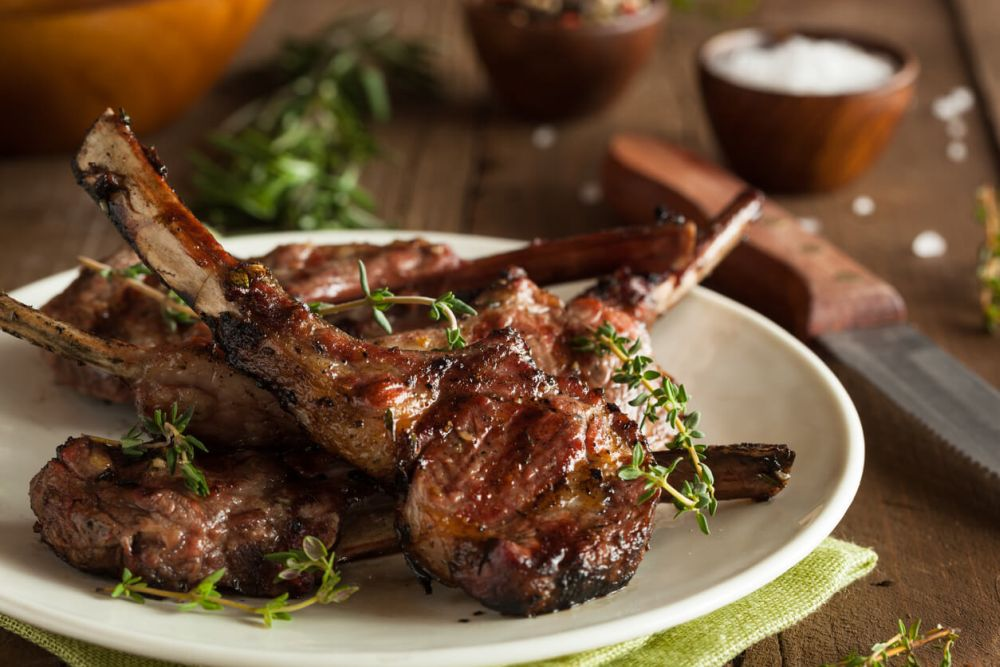 Grilled lamb chops organized on a white plate on wood