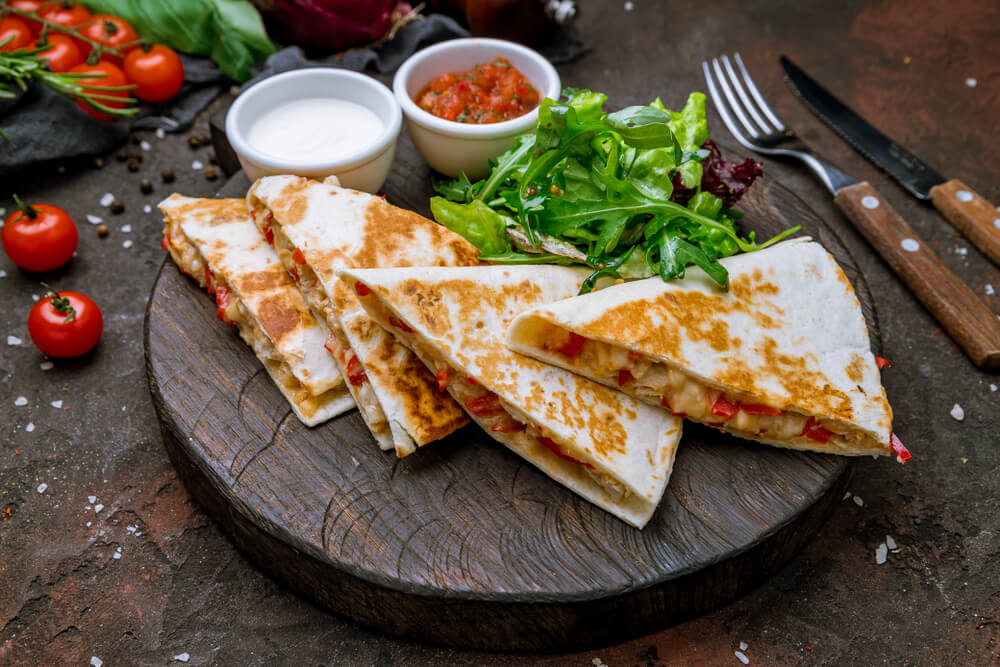Quesadilla With Chicken and Sauces on Dark Board