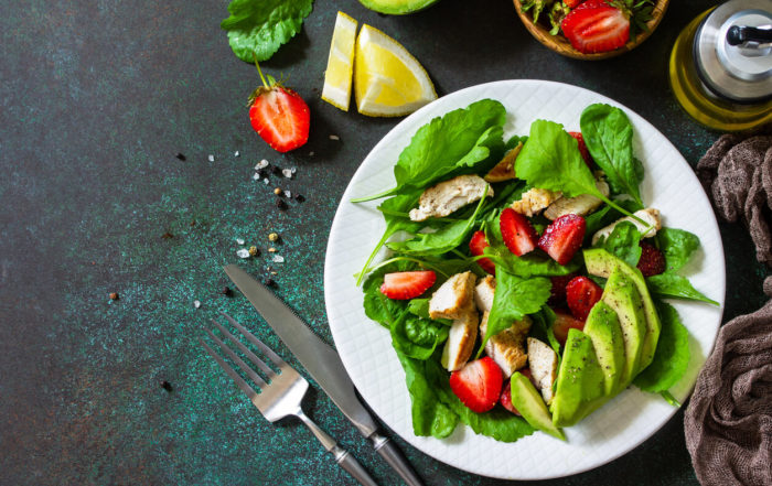 Summer Salad With Strawberries, Grilled Chicken and Avocado on a Stone Table.