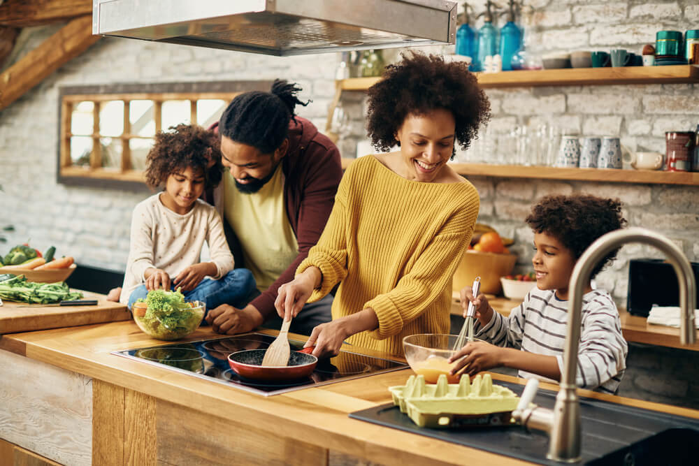 Happy Parents and Their Kids Preparing Food in the Kitchen.